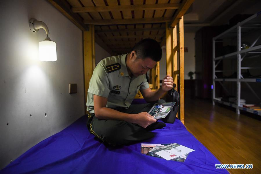 Wang Zhiguo looks at family photos in the dormitory in Nanjing, capital of east China\'s Jiangsu Province, Aug. 7, 2018. Wang Jicai, who used to be head of the militia post on Kaishan Island in Jiangsu Province, started working on the island in the Yellow Sea with his wife in 1986. He died of sudden illness while on duty in July of 2018 at the age of 58. Wang Zhiguo, son of Wang Jicai, became a frontier defence policeman after his graduation from Nanjing University of Aeronautics and Astronautics in 2013. He had been assigned to many security tasks for major events during 5 years\' working. (Xinhua/Li Xiang)