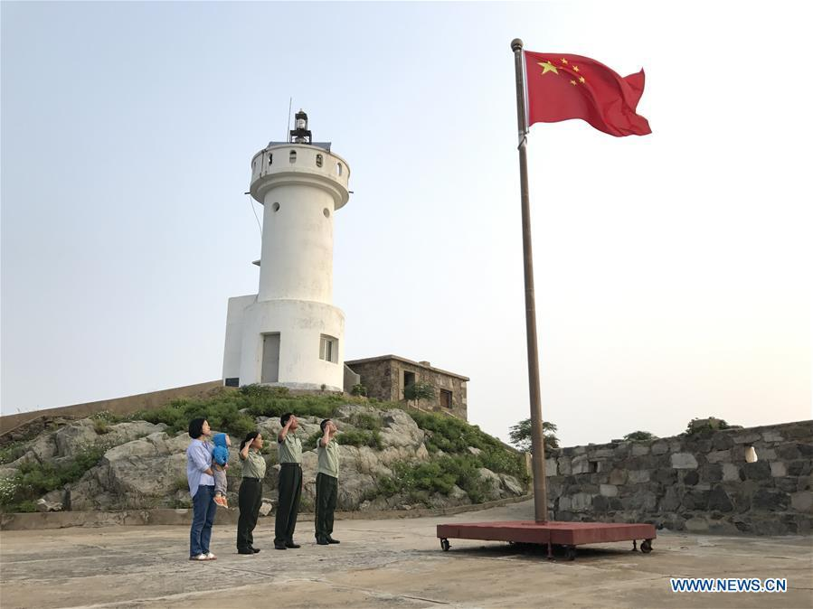 Wang Zhiguo (1st R) salutes the national flag with his family on Kaishan Island of Guanyun County, east China\'s Jiangsu Province, Sept. 12, 2017. Wang Jicai, who used to be head of the militia post on Kaishan Island in Jiangsu Province, started working on the island in the Yellow Sea with his wife in 1986. He died of sudden illness while on duty in July of 2018 at the age of 58. Wang Zhiguo, son of Wang Jicai, became a frontier defence policeman after his graduation from Nanjing University of Aeronautics and Astronautics in 2013. He had been assigned to many security tasks for major events during 5 years\' working. (Xinhua/Li Xiang)