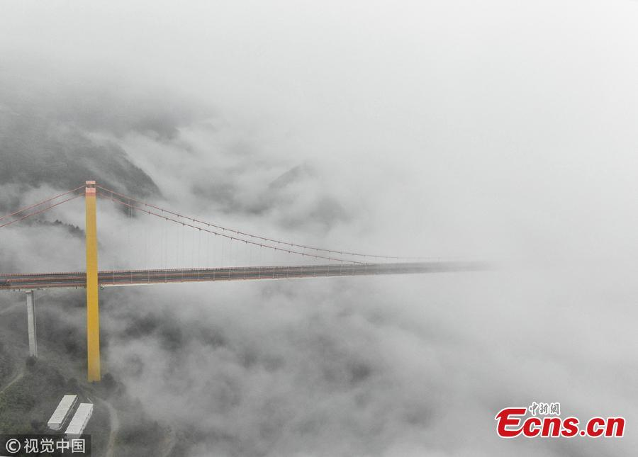 Clouds surround the Puli Bridge, which connects Guizhou and Yunnan provinces in southwest China. The bridge, one of the world\'s highest, stands hundreds of meters above the Beipan River and links Duge of Guizhou and Puli of Yunnna, attracting tourists with its stunning views. (Photo/VCG)
