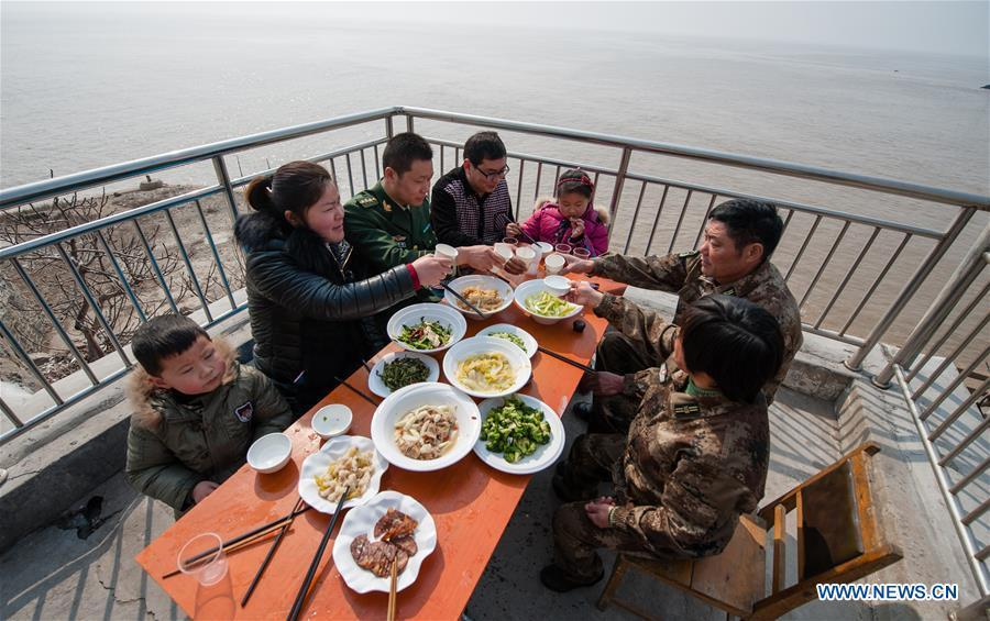 Wang Zhiguo (3rd L) enjoys dinner with family members on Kaishan Island of Guanyun County, east China\'s Jiangsu Province, Feb. 13, 2015. Wang Jicai, who used to be head of the militia post on Kaishan Island in Jiangsu Province, started working on the island in the Yellow Sea with his wife in 1986. He died of sudden illness while on duty in July of 2018 at the age of 58. Wang Zhiguo, son of Wang Jicai, became a frontier defence policeman after his graduation from Nanjing University of Aeronautics and Astronautics in 2013. He had been assigned to many security tasks for major events during 5 years\' working. (Xinhua/Li Xiang)