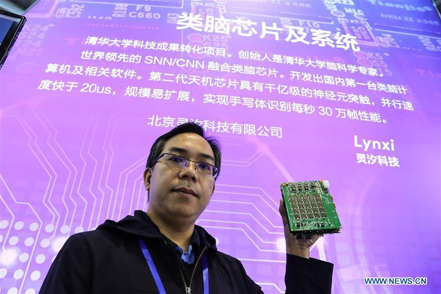 A staff member shows a deep learning chipset during a press preview of the 2018 National Mass Innovation and Entrepreneurship Week in Beijing, capital of China, Oct. 8, 2018. The weekly event will run from October 9 to 15. (Xinhua/Zhang Yuwei)