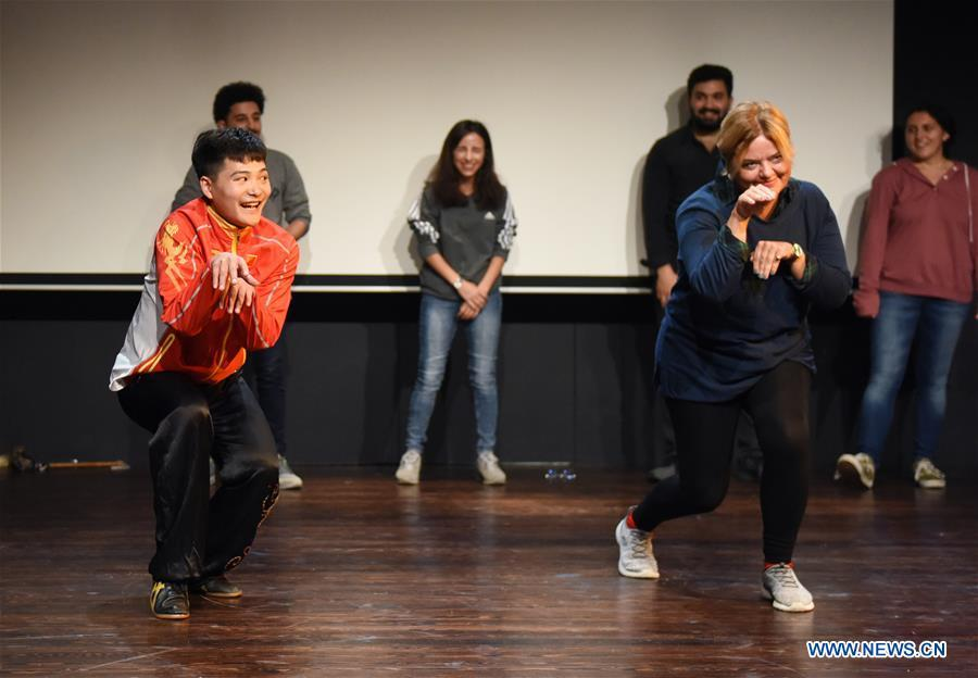 Shi Longlong (L, Front), a teacher of the Beijing-based Capital University of Physical Education and Sports, teaches a Turkish woman Kung Fu moves in Bogazici University of Istanbul, Turkey, on Oct. 9, 2018. A charm of Chinese Kung Fu tour started on Tuesday evening at Bogazici University in Istanbul, enchanting the audience with a mixture of Chinese martial arts and dances. (Xinhua/He Canling)
