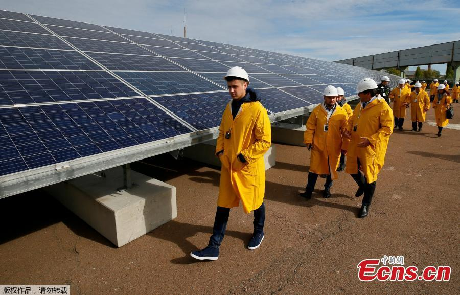 Visitors walk by the photovoltaic panels during an official opening ceremony of the new one-megawatt solar power plant \'\'Solar Chernobyl\