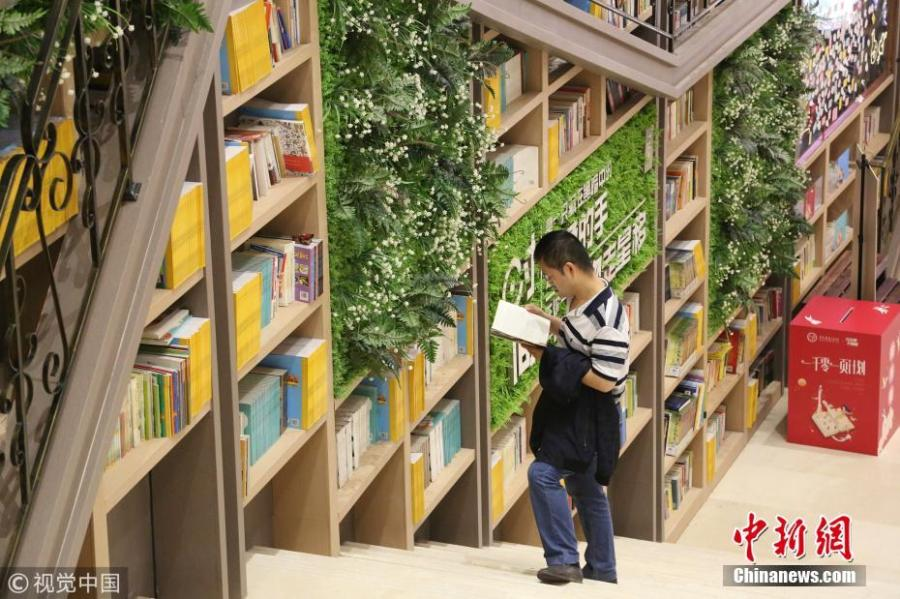 Tens of thousands of books are placed on shelves to form a 10-meter-tall books wall inside a shopping center in Chongqing, Oct. 10, 2018. (Photo/VCG)