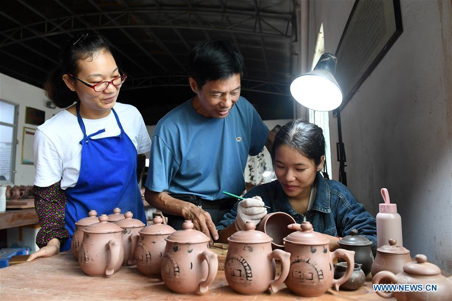 Zhang Chuanrui (C), an experienced Nixing pottery artisan, gives instructions to a staff member at a workshop in Qinzhou, south China\'s Guangxi Zhuang Autonomous Region, Oct. 9, 2018. The making of Nixing pottery is a well-preserved tradition in Qinzhou. In 2008, the techniques of making Nixing pottery were listed as one of China\'s state-level intangible cultural heritages. Currently, over 10,000 workers are engaged in the Nixing pottery industry in Qinzhou, producing more than 1,000 pottery varieties. (Xinhua/Lu Boan)