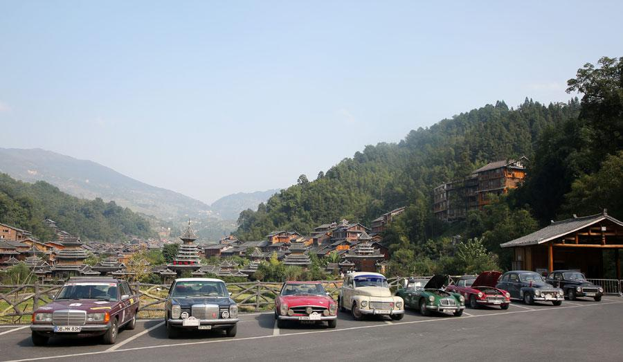 Vintage cars park at a Dong ethnic village in Liping, Southwest China\'s Guizhou province on Oct. 8, 2018. The trip was initiated by 34 drivers from Germany and Switzerland. (Photo provided to chinadaily.com.cn)