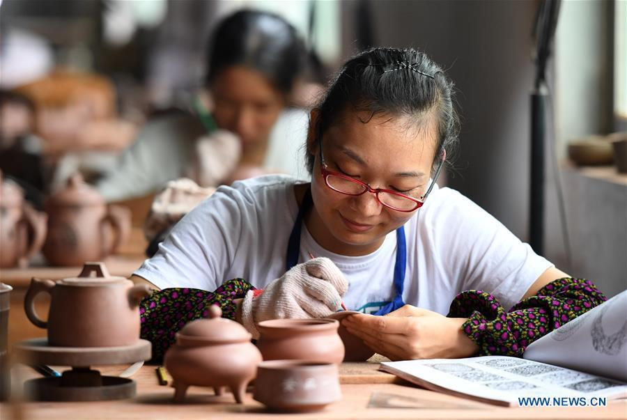 A staff member works on a Nixing pottery ware at a workshop in Qinzhou, south China\'s Guangxi Zhuang Autonomous Region, Oct. 9, 2018. The making of Nixing pottery is a well-preserved tradition in Qinzhou. In 2008, the techniques of making Nixing pottery were listed as one of China\'s state-level intangible cultural heritages. Currently, over 10,000 workers are engaged in the Nixing pottery industry in Qinzhou, producing more than 1,000 pottery varieties. (Xinhua/Lu Boan)