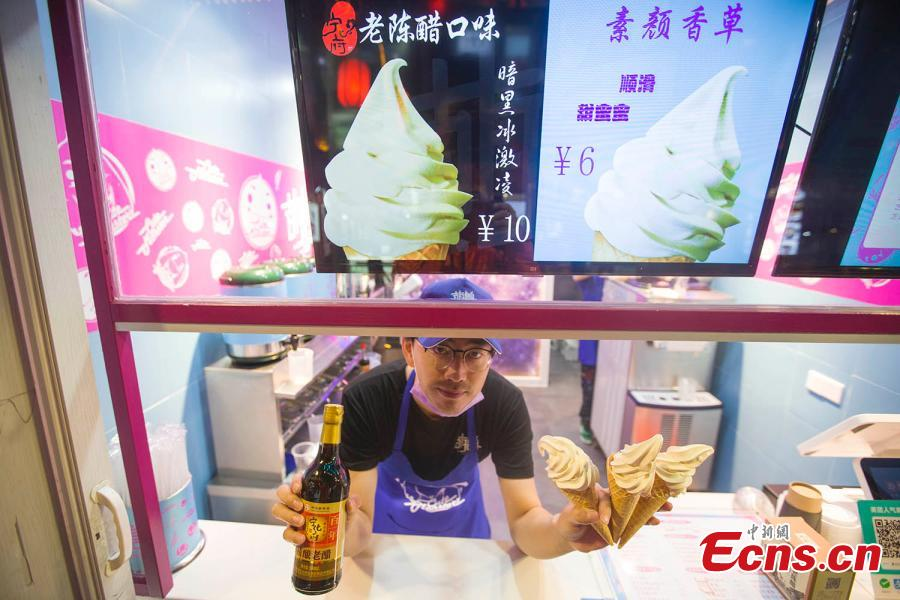 A man shows ice cream flavored with mature vinegar in Taiyuan, capital of north China\'s Shanxi Province, October 9, 2018. (Photo: China News Service/ Zhang Yun)