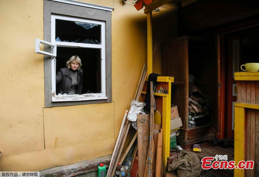 Local resident Valentyna Petrenko, 52, looks out of a broken window of her house in the settlement of Druzhba, located near the scene of explosions at a defence ministry ammunition depot in the eastern Chernihiv region, Ukraine, Oct. 9, 2018. Ukrainian authorities suspect sabotage lay behind explosions that tore through an ammunition depot in the early hours of Tuesday, sending fireballs into the sky and causing more than 12,000 people to be evacuated. (Photo/Agencies)