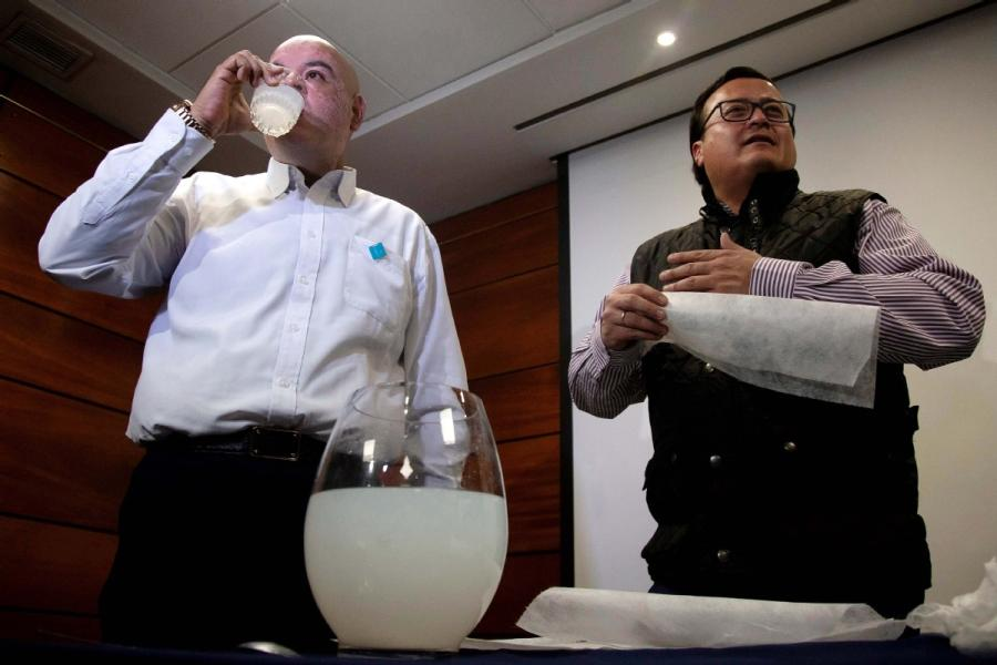 Chilean entrepreneur Roberto Astete (left) stands with Olivares and drinks a solution of water and dissolved PVA to prove it is safe to consume the mixture. (CLAUDIO REYES/FOR CHINA DAILY)