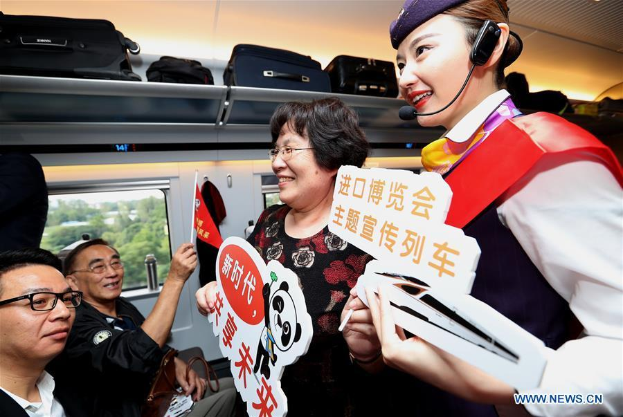 A railway attendant briefs passengers on information about the first China International Import Expo (CIIE) on board the G2 bullet train in east China\'s Shanghai, Oct. 10, 2018. Railway authorities have launched a campaign on Wednesday to promote the upcoming first CIIE on bullet trains running on the Beijing-Shanghai high-speed railway. (Xinhua/Chen Fei)