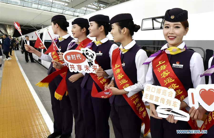 Attendants of the G2 bullet train hold sign boards to promote the first China International Import Expo (CIIE) at Hongqiao Railway Station in east China\'s Shanghai, Oct. 10, 2018. Railway authorities have launched a campaign on Wednesday to promote the upcoming first CIIE on bullet trains running on the Beijing-Shanghai high-speed railway. (Xinhua/Chen Fei)