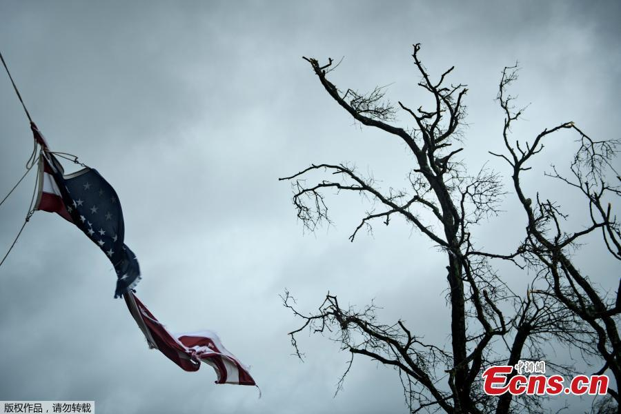 An American flag is torn during Hurricane Michael October 10, 2018 in Panama City, Florida. Michael slammed into the Florida coast on October 10 as the most powerful storm to hit the southern US state in more than a century as officials warned it could wreak \