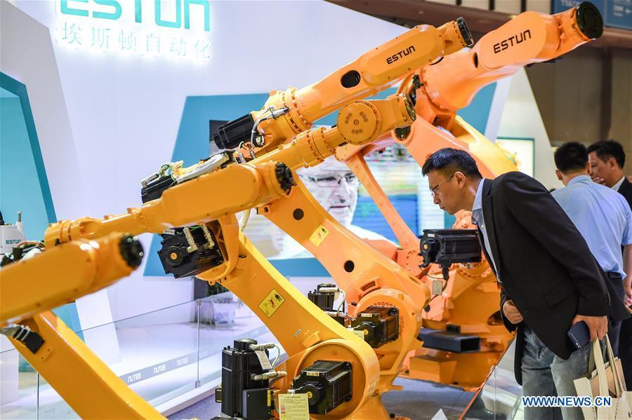 A visitor looks at an automatic robot during the World Intelligent Manufacturing Summit (WIMS) 2018 in Nanjing, east China\'s Jiangsu Province, Oct. 11, 2018. The WIMS 2018 opened at the Nanjing International Expo Center on Thursday. The event attracts over 1,900 exhibitors worldwide to showcase the latest technologies, advanced products, development trends and cutting-edge solutions in the intelligent manufacturing field. (Xinhua/Li Bo)
