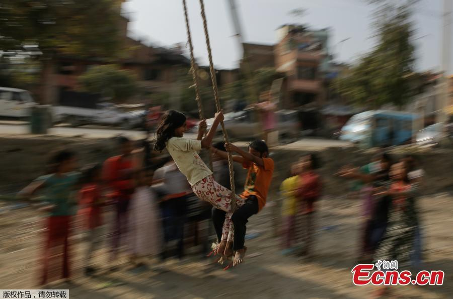 Two children play on a swing, popularly known as the \'Dashain Ping\', ahead of the Hindu festival of Dashain in Kathmandu, Nepal, Oct. 11, 2018. People of all ages often play on a swing in towns and villages during the celiebration of the festival. (Photo: China News Service/Pu Ladan)