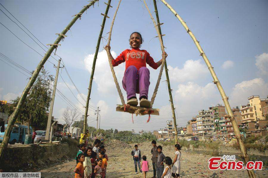 A child plays on a swing, popularly known as the \'Dashain Ping\', ahead of the Hindu festival of Dashain in Kathmandu, Nepal, Oct. 11, 2018. People of all ages often play on a swing in towns and villages during the celiebration of the festival. (Photo: China News Service/Pu Ladan)