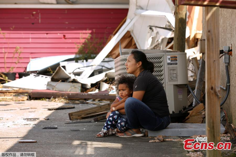 Wimlin Washington and her 3-year-old daughter Mia sit in front of their restaurant, damaged by Hurricane Michael in Callaway, Florida, U.S. October 11, 2018. (Photo/Agencies)