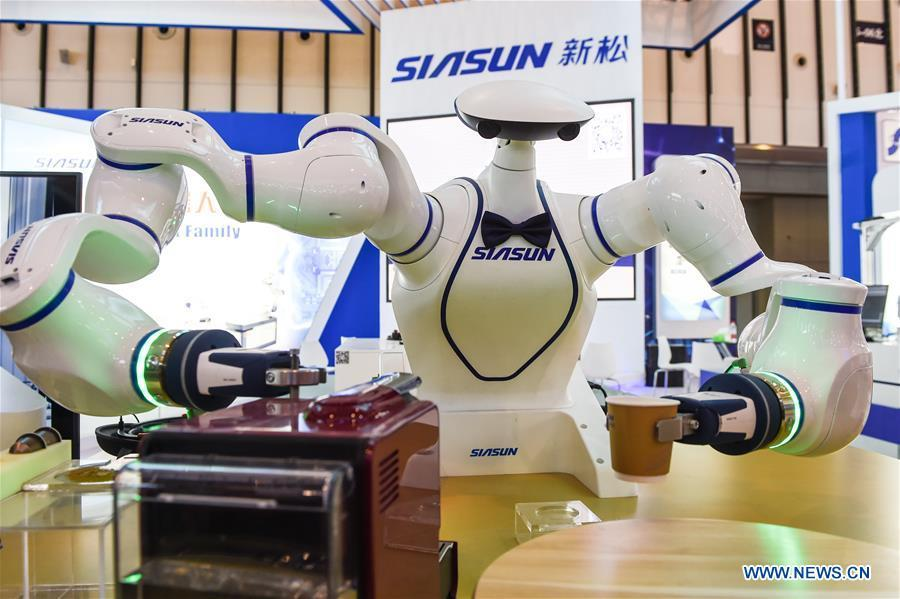 A dual-arm assistant robot makes coffee during the World Intelligent Manufacturing Summit (WIMS) 2018 in Nanjing, east China\'s Jiangsu Province, Oct. 11, 2018. The WIMS 2018 opened at the Nanjing International Expo Center on Thursday. The event attracts over 1,900 exhibitors worldwide to showcase the latest technologies, advanced products, development trends and cutting-edge solutions in the intelligent manufacturing field. (Xinhua/Li Bo)