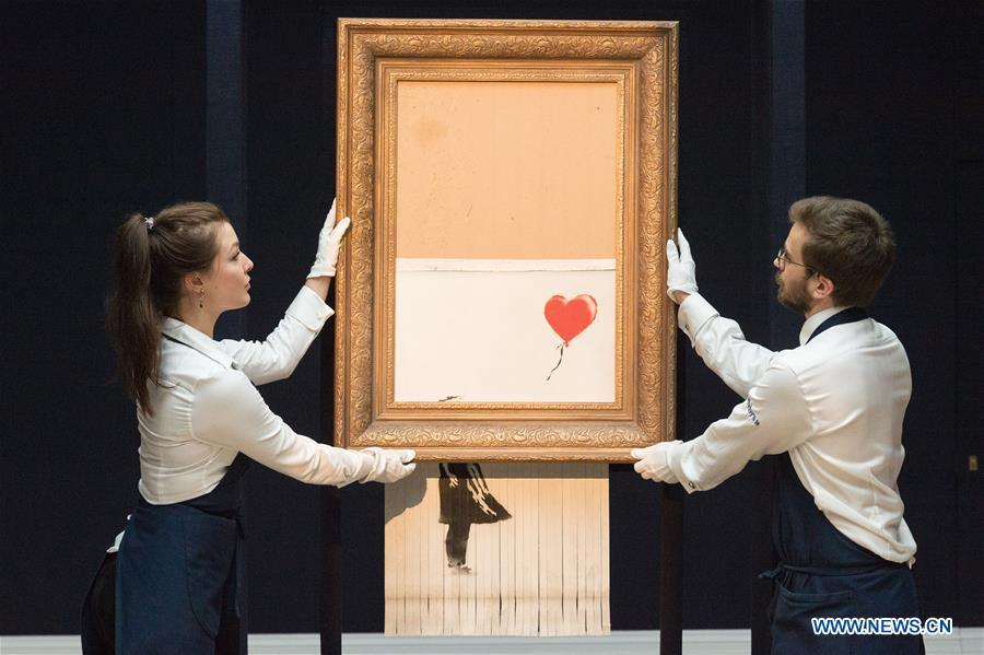 Sotheby\'s staff members present Banksy\'s \