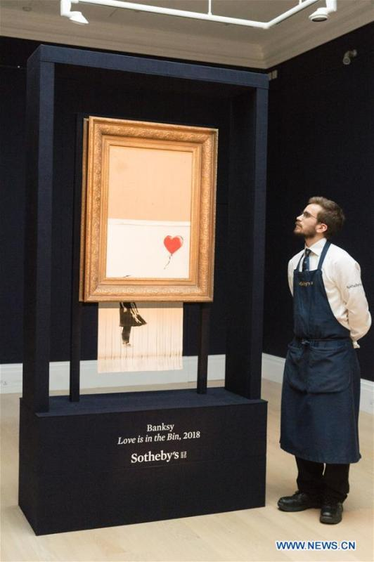 A staff member of Sotheby\'s presents Banksy\'s \