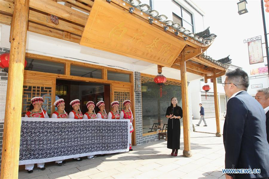 A guest is welcomed by women of Bai ethnic group at the door of a tea house at the Suoziqiu Village of Mahekou Township in Sangzhi County of Zhangjiajie City, central China\'s Hunan Province, Oct. 11, 2018. People of the Bai ethnic group here still follow the welcoming tradition of their immigrated ancestors to offer \