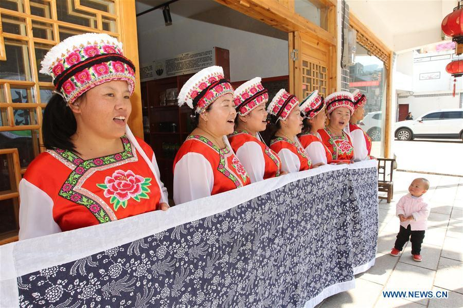 Women of Bai ethnic group sing a welcoming song for guests at the door of a tea house at the Suoziqiu Village of Mahekou Township in Sangzhi County of Zhangjiajie City, central China\'s Hunan Province, Oct. 11, 2018. People of the Bai ethnic group here still follow the welcoming tradition of their immigrated ancestors to offer \