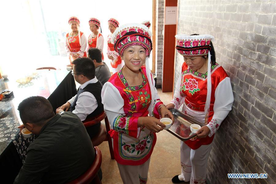 Women of Bai ethnic group serve tea to guests at a tea house at the Suoziqiu Village of Mahekou Township in Sangzhi County of Zhangjiajie City, central China\'s Hunan Province, Oct. 11, 2018. People of the Bai ethnic group here still follow the welcoming tradition of their immigrated ancestors to offer \