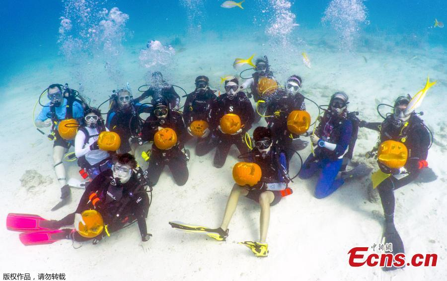 Contestants show their Halloween creations about nine meters beneath the ocean\'s surface in the Underwater Pumpkin Carving Contest, staged by the Amoray Dive Resort off Key Largo, Florida, in the Florida Keys National Marine Sanctuary, Oct. 14, 2018. (Photo/Agencies)