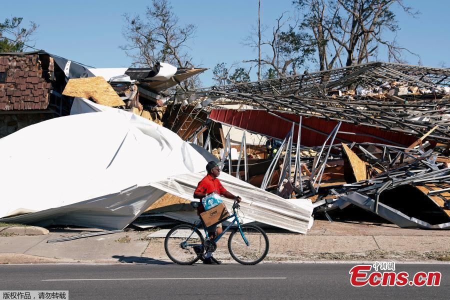 A man carries food and water past a building damaged by Hurricane Michael in Parker, Florida, U.S., October 13, 2018. Dozens of people remained missing on Sunday in Florida Panhandle communities reduced to ruins by Hurricane Michael as rescuers said they expected the death toll to rise and survivors grappled with power outages and shortages of food and water. (Photo/Agencies)