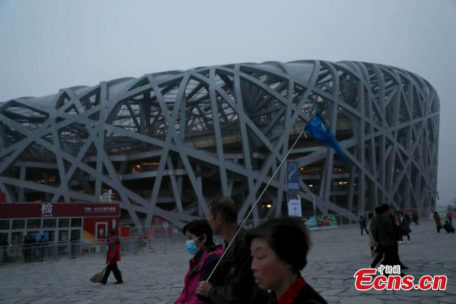 Tourists visit the area around National Stadium, also known as the Bird\'s Nest, on a smoggy day in Beijing, Oct. 14, 2018. Serious air pollution was reported in Beijing on Sunday. (Photo: China News Service/Liu Guanguan)