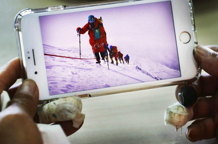 Xia looks at the photos and recalls the experience of climbing Qomolangma.(Photo/China Daily)