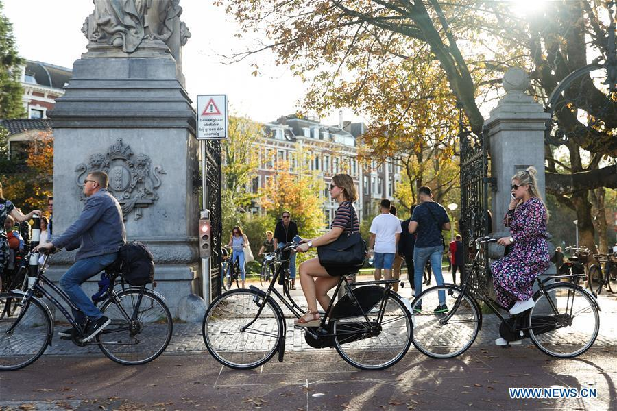 People ride bicycles on a street in Amsterdam, the Netherlands, Oct. 13, 2018. (Xinhua/Zheng Huansong)