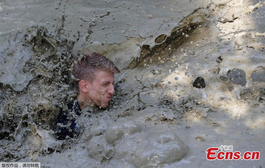 A competitor crosses a water obstacle during the \'Wild Boar Dirt Run\' (Wildsau Dirt Run) near Brand-Laaben, Austria, October 13, 2018. People took part in a hard obstacle course in three distances 5, 10 and 20 kilometers. (Photo/Agencies)