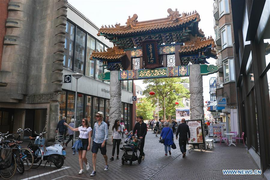 People walk through the traditional Chinese archway at the Chinatown in The Hague, the Netherlands, on Oct. 13, 2018. The Hague\'s Chinatown is located in the downtown area of the city. With red lanterns, Chinese restaurants, Chinese medicine service shops and other shops featuring Chinese culture, the street attracts many citizens and worldwide tourists. (Xinhua/Zheng Huansong)