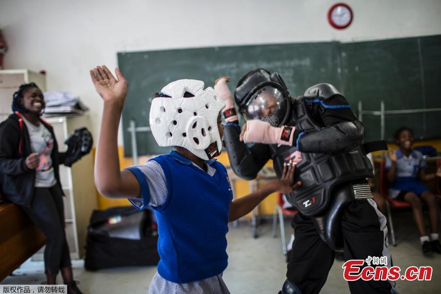 Girls practice self-defense methods on one of the instructors dressed in protective gear during a session with NGO Action Breaks Silence (ABS) called \'Empowerment through self-defense for women and girls\' which aims to create a world free form fear of gender based violence, on October 10, 2018, at Mbuyisa Makhubu Primary School in the area of Orlando West, in the South African township of Soweto. (Photo/Agencies)