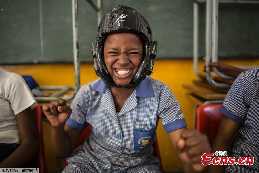 Phumzile Mapisa, 12, poses while wearing a helmet during a session with NGO Action Breaks Silence (ABS) called \'Empowerment through self-defense for women and girls\' which aims to create a world free form fear of gender based violence, on October 10, 2018, at Mbuyisa Makhubu Primary School in the area of Orlando West, in the South African township of Soweto. (Photo/Agencies)