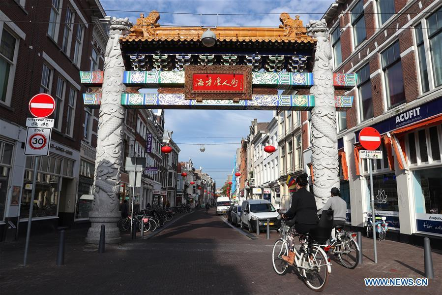 People ride bikes through the traditional Chinese archway at the Chinatown in The Hague, the Netherlands, on Oct. 15, 2018. The Hague\'s Chinatown is located in the downtown area of the city. With red lanterns, Chinese restaurants, Chinese medicine service shops and other shops featuring Chinese culture, the street attracts many citizens and worldwide tourists. (Xinhua/Zheng Huansong)