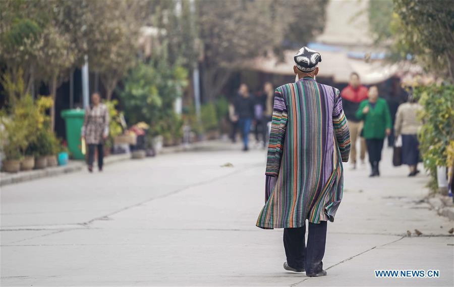 An elderly man dressed in traditional costume walks on a street in Kashgar City, northwest China\'s Xinjiang Uygur Autonomous Region, Oct. 16, 2018. The ancient oasis city of Kashgar, in the westernmost part of China near the border with Kyrgyzstan, Tajikistan, Afghanistan, and Pakistan, was an important staging post on the original Silk Road and has been revitalized as a bustling hub of business and different cultures. (Xinhua/Hu Huhu)
