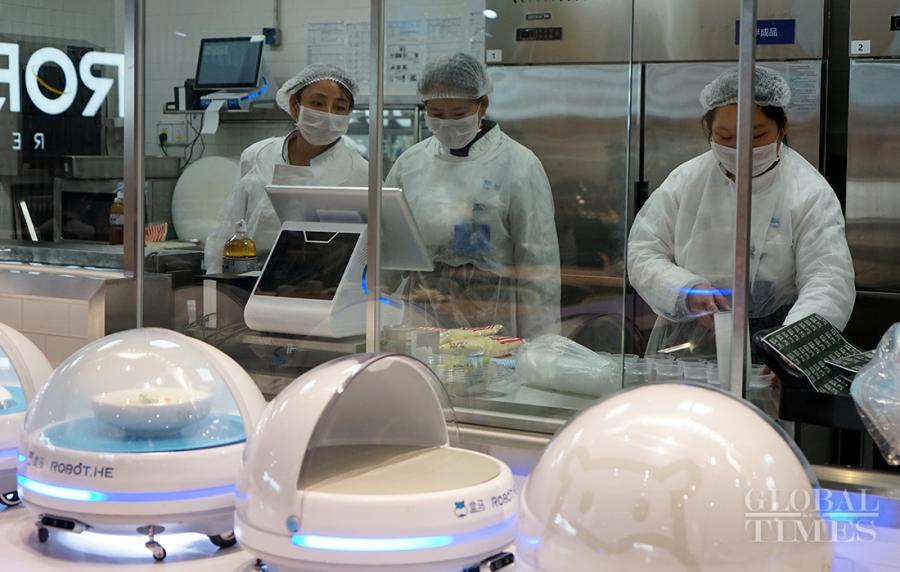 Robots wait for the finished dishes before delivering to hungry customers.  (Photos: Yang Hui/GT)