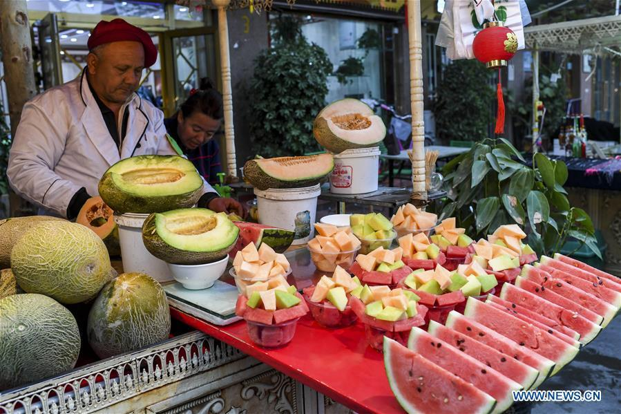 A vendor sells fruits at a night market in Kashgar City, northwest China\'s Xinjiang Uygur Autonomous Region, Oct. 16, 2018. The ancient oasis city of Kashgar, in the westernmost part of China near the border with Kyrgyzstan, Tajikistan, Afghanistan, and Pakistan, was an important staging post on the original Silk Road and has been revitalized as a bustling hub of business and different cultures. (Xinhua/Hu Huhu)