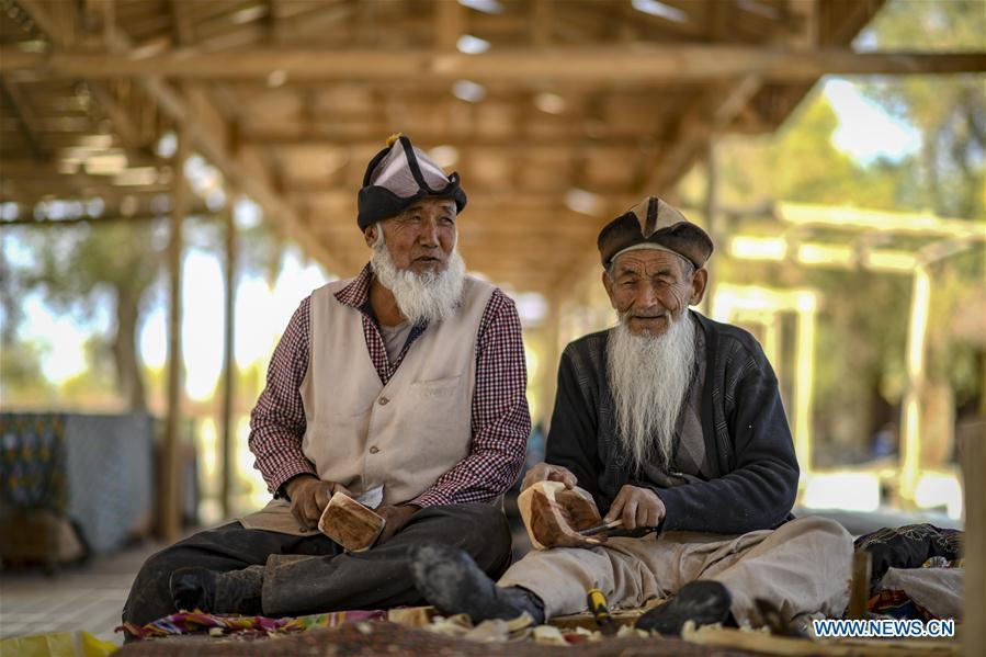 Two residents make models of a special kind of dugout canoe made of desert poplar in Lop Nur People Village of Yuli County, northwest China\'s Xinjiang Uygur Autonomous Region, Oct. 16, 2018. The Lop Nur people depended basically on fishing for livelihood and developed a distinct culture based on their special lifestyle. Located in Tarim basin, Yuli is known for its natural scenery and ethnic culture and keeps attracting numerous tourists from at home and abroad. From Oct. 1 to 16, 2018, Yuli County has received more than 230,000 visitors, with a year-on-year increase of 31.46 percent. (Xinhua/Zhao Ge)