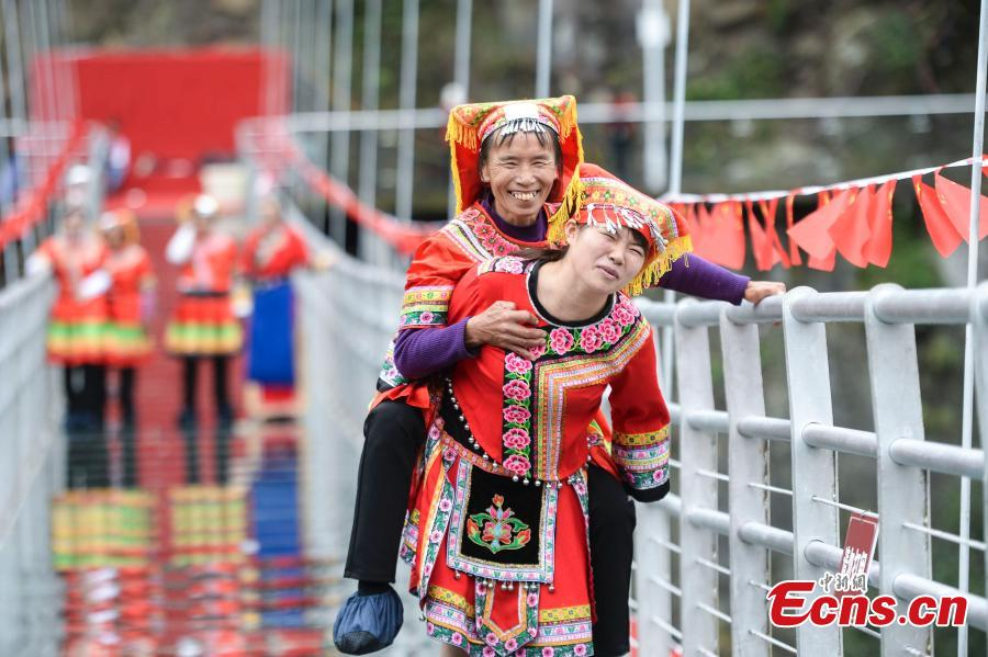 Women carrying their mothers-in-law on their back compete in a race on the 140-meter-long glass bridge in Jiulong River National Forest Park in Hunan Province, Oct. 16, 2018, ahead of the Double Nine Festival. Women from the She and Yao ethnic groups participated the competition. The 9th day of the 9th lunar month is the traditional Chongyang Festival, or Double Nine Festival, which falls on Oct. 17 this year. (Photo: China News Service/Yang Huafeng)
