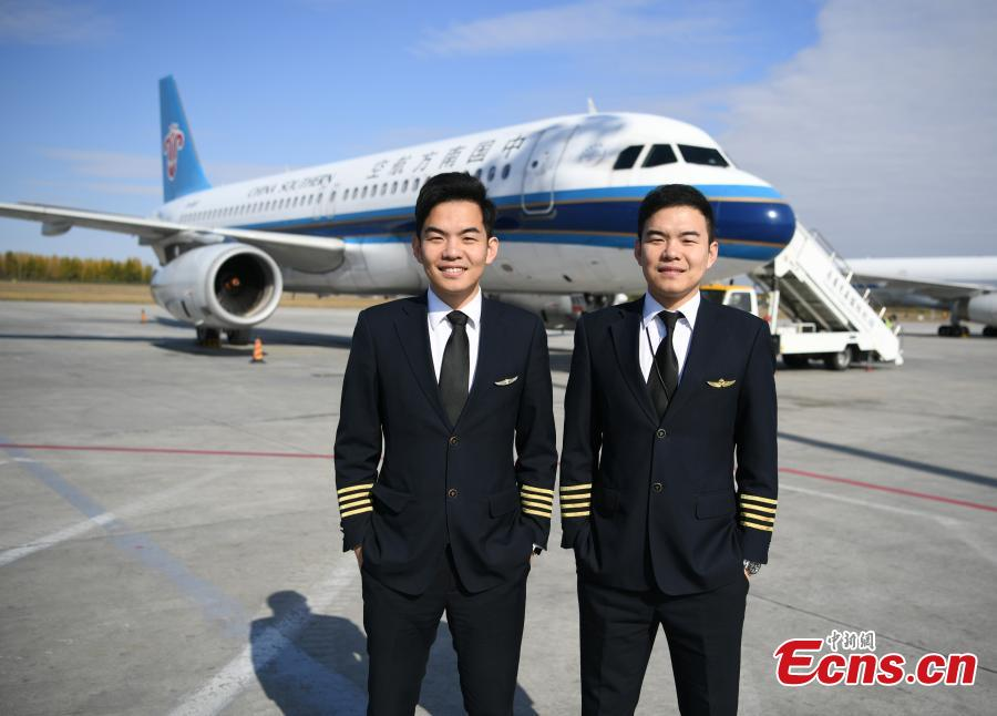 Twin brothers Liu Ke (L) and Liu Xin pose for a photo near a China Southern Airlines aircraft on Oct. 16, 2018. The twin brothers, born in 1987, were from a young age both interested in becoming pilots. After graduating high school, they both went on to study at the Civil Aviation Flight University of China. Later, both became pilots for China Southern Airlines. (Photo: China News Service/Zhang Yao)