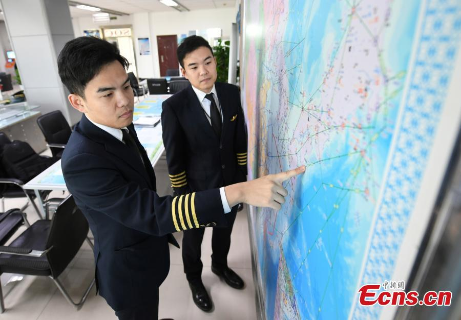 Twin brothers Liu Ke (L) and Liu Xin study a flight map on Oct. 16, 2018. The twin brothers, born in 1987, were from a young age both interested in becoming pilots. After graduating high school, they both went on to study at the Civil Aviation Flight University of China. Later, both became pilots for China Southern Airlines. (Photo: China News Service/Zhang Yao)