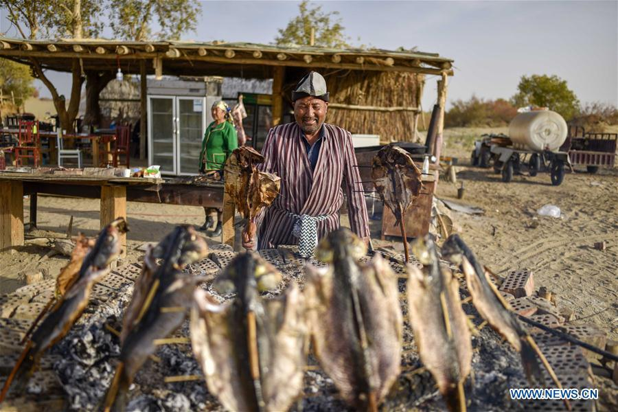 A resident makes roast fish at the Lop Nur People Village of Yuli County, northwest China\'s Xinjiang Uygur Autonomous Region, Oct. 16, 2018. The Lop Nur people depended basically on fishing for livelihood and developed a distinct culture based on their special lifestyle. Located in Tarim basin, Yuli is known for its natural scenery and ethnic culture and keeps attracting numerous tourists from at home and abroad. From Oct. 1 to 16, 2018, Yuli County has received more than 230,000 visitors, with a year-on-year increase of 31.46 percent. (Xinhua/Zhao Ge)