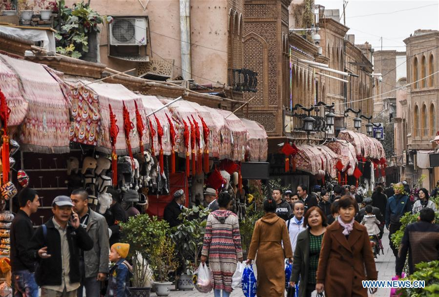 People walk on a shopping street in Kashgar City, northwest China\'s Xinjiang Uygur Autonomous Region, Oct. 16, 2018. The ancient oasis city of Kashgar, in the westernmost part of China near the border with Kyrgyzstan, Tajikistan, Afghanistan, and Pakistan, was an important staging post on the original Silk Road and has been revitalized as a bustling hub of business and different cultures. (Xinhua/Li Zhihao)