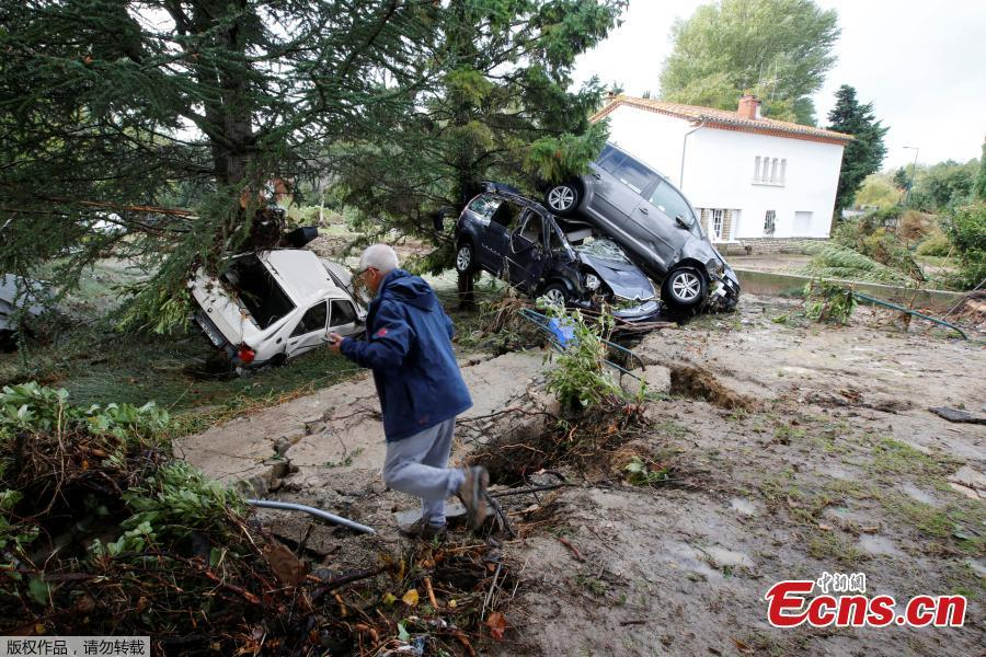 A man walks near damaged cars as clean-up operations continue the day after some of the worst flash floods in a century turned rivers into raging torrents that engulfed homes and swept away cars hit the southwestern Aude district of France, in Conques, France, Oct. 16, 2018. At least 12 people died. (Photo/Agencies)