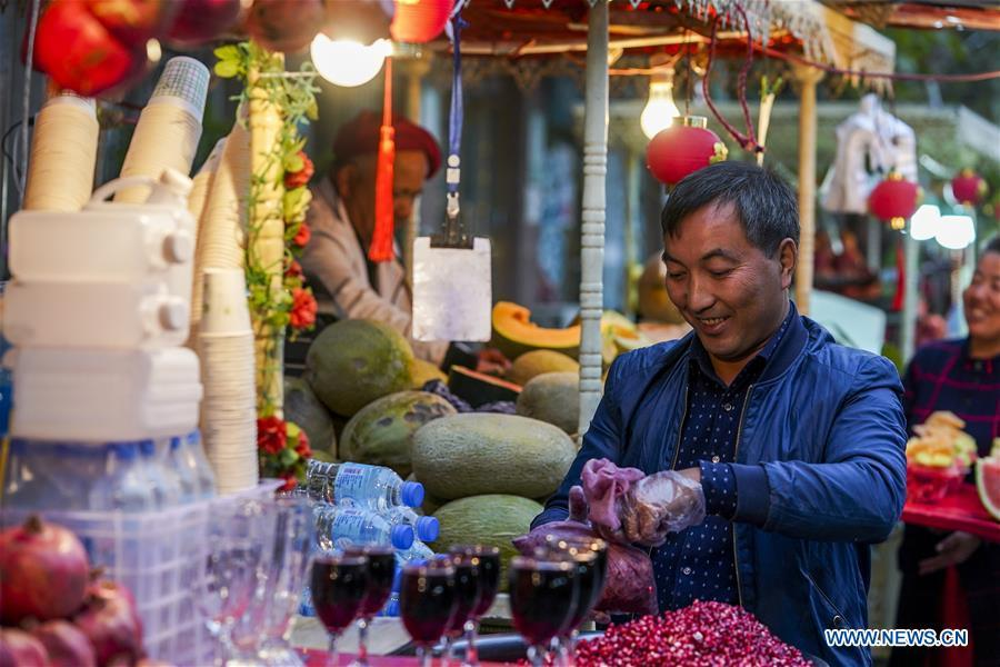 A fruit vendor juices pomegranates at a night market in Kashgar City, northwest China\'s Xinjiang Uygur Autonomous Region, Oct. 16, 2018. The ancient oasis city of Kashgar, in the westernmost part of China near the border with Kyrgyzstan, Tajikistan, Afghanistan, and Pakistan, was an important staging post on the original Silk Road and has been revitalized as a bustling hub of business and different cultures. (Xinhua/Hu Huhu)