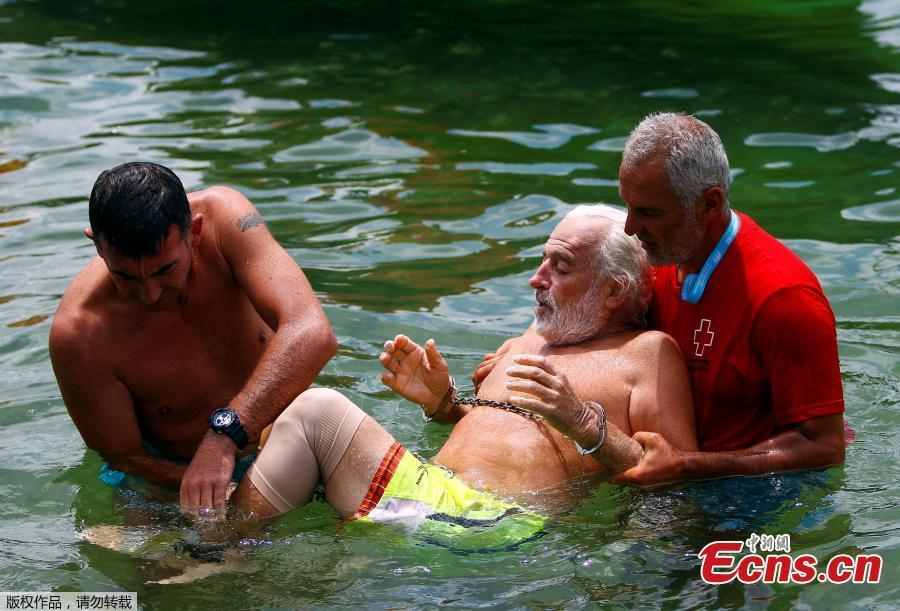 Bulgarian Jane Petkov, 64, is held after he wanted to set a new Guinness World Record by attempting to swim more than three kilometers at Macedonia\'s Lake Ohrid,? in a bag with his arms and legs tied up, in Ohrid, Macedonia, July 24, 2018. (Photo/Agencies)