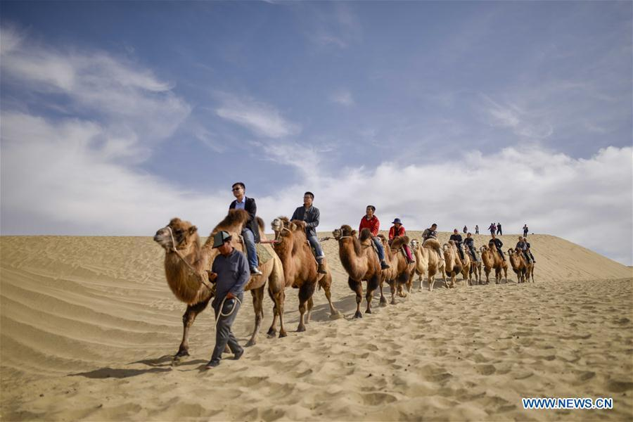 Tourists ride camels in Lop Nur People Village of Yuli County, northwest China\'s Xinjiang Uygur Autonomous Region, Oct. 16, 2018. The Lop Nur people depended basically on fishing for livelihood and developed a distinct culture based on their special lifestyle. Located in Tarim basin, Yuli is known for its natural scenery and ethnic culture and keeps attracting numerous tourists from at home and abroad. From Oct. 1 to 16, 2018, Yuli County has received more than 230,000 visitors, with a year-on-year increase of 31.46 percent. (Xinhua/Zhao Ge)